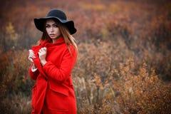 Frau in einem roten Mantel lizenzfreie stockbilder