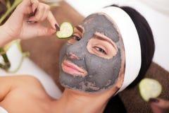 Frau in einem Schönheitssalon, Wellness Kosmetisches Verfahrensfrau ` s Gesicht in der Maskenabschwächung und in den Gurkenscheib Lizenzfreie Stockfotografie