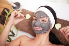 Frau in einem Schönheitssalon, Wellness Kosmetisches Verfahrensfrau ` s Gesicht in der Maskenabschwächung und in den Gurkenscheib Stockfotos