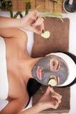 Frau in einem Schönheitssalon, Wellness Kosmetisches Verfahrensfrau ` s Gesicht in der Maskenabschwächung und in den Gurkenscheib Stockbilder