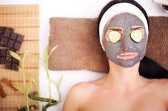 Frau in einem Schönheitssalon, Wellness Kosmetisches Verfahrensfrau ` s Gesicht in der Maskenabschwächung und in den Gurkenscheib Lizenzfreie Stockbilder