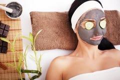 Frau in einem Schönheitssalon, Wellness Kosmetisches Verfahrensfrau ` s Gesicht in der Maskenabschwächung und in den Gurkenscheib Stockfotografie