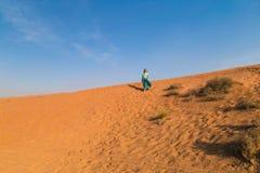 Frau in einem schlammigen Türkisrock mit einer Verzierung und einem monophonischen Türkishemd eine an der Spitze der orange Dünen stockfotografie
