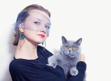 Frau in einem Schleier, der graue britische Katze anhält stockbilder