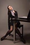 Frau in einem schwarzen Anzug, der auf einem Bürotisch sitzt Stockbild
