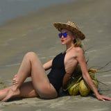 Frau in einem schwarzen Badeanzug und in einem Hut, die auf dem tropischen Strand sich entspannen Stockbild