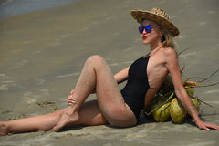 Frau in einem schwarzen Badeanzug und in einem Hut, die auf dem tropischen Strand sich entspannen Stockfoto