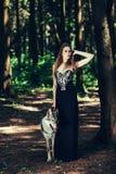 Frau in einem schwarzen Kleid mit einem Hund lizenzfreies stockfoto