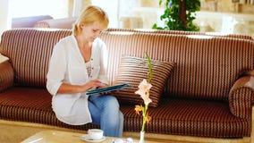 Frau in einem Sommerhemd benutzt eine Tablette in der Hotellobby stock video footage