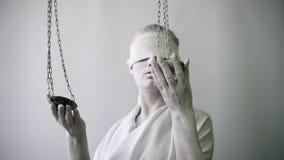 Frau in einem Steinstatuenkostüm Femida die Göttin von Gerechtigkeit auf einem weißen Hintergrund in einer Hand, welche die Skale stock footage