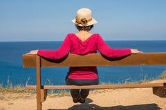Frau in einem Strohhut betrachtet das Meer Stockbild