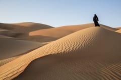 Frau in einem traditionellen emirati Kleid in einer Wüste Lizenzfreie Stockfotografie