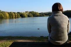 Frau in einem warmen Pullover, der allein durch einen See sitzt lizenzfreies stockfoto