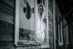 Frau in einem wei?en Hemd nahe dem Fenster lizenzfreie stockfotos