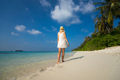 Frau in einem weißen Kleid auf dem tropischen Strand Stockfoto