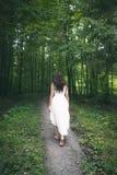Frau in einem weißen Kleid gehend durch einen Wald Stockfotos