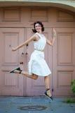 Frau in einem weißen Kleid lächelt und springt nahe der alten Tür Stockfotos