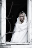 Frau in einem weißen Blatt nahe dem Fenster Stockfoto