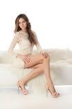 Frau in einem weißen Kleid auf einem weißen Sofa Stockfotos