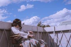 Frau in einem Weinlesekleid, das auf dem Dach eines Gebäudes mit einem schönen blauen Himmel und Wolken sitzt stockbild