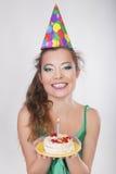 Frau in einer Geburtstags-Kappe, welche die Kerze auf Kuchen durchbrennt Lizenzfreie Stockfotografie