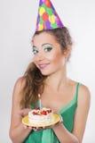 Frau in einer Geburtstags-Kappe, welche die Kerze auf Kuchen durchbrennt Lizenzfreie Stockfotos