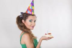 Frau in einer Geburtstags-Kappe, welche die Kerze auf Kuchen durchbrennt Stockfotos