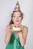 Frau in einer Geburtstags-Kappe, welche die Kerze auf Kuchen durchbrennt Stockfotografie