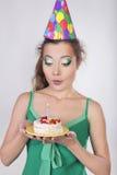 Frau in einer Geburtstags-Kappe, welche die Kerze auf Kuchen durchbrennt Stockfoto