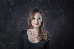 Frau in einer guten Laune und in einem Lächeln Noir Filmartfrau im eleganten Kleid und in der Halskette Schönes Tanzen der jungen Lizenzfreie Stockfotografie