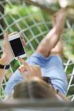 Frau in einer Hängematte mit Handy an einem Sommertag Stockbilder