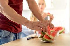 Frau in einer Küche rote Wassermelone essend und ihren Ehemann, Paar betrachtend in ihrer großen zeitgenössischen weißen Küche Stockbild