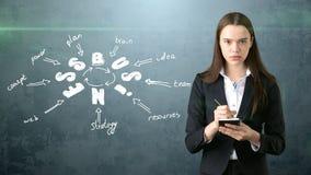 Frau in einer Klage, die Notizbuch nahe der Wand mit einer Geschäftsideenskizze gezeichnet auf sie hält Konzept eines erfolgreich Lizenzfreie Stockfotografie