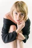 Frau in einer losen, großen schwarzen Strickjacke, die oben schaut Lizenzfreie Stockbilder