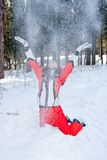 Frau in einer sportlichen Klage wirft herauf Schnee In-field Stockbild
