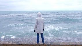Frau in einer weißen Jacke steht auf der Ufergegend auf den ausgestreckten Strandarmen und betrachtet Sturmwellen Rückseitige Ans stock footage