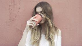 Frau in einer weißen Strickjacke trinkt einen Kaffee zum Mitnehmen und schaut zur Kamera stock video
