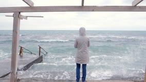 Frau in einer weißen Jacke nimmt einem Handy die großen Sturmwellen, die auf Damm stehen Rückseitige Ansicht stock video