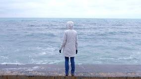Frau in einer weißen Jacke steht auf der Ufergegend auf den Strandblicken an den Sturmwellen Rückseitige Ansicht stock video