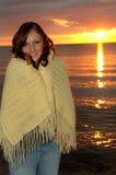 Frau eingewickelt in der Decke am Sonnenuntergang Stockfotografie