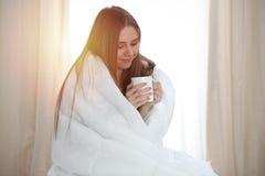 Frau eingewickelt in einer Decke und in den Griffen, die ein Becher nach aufwachen, einen Tag glücklich und entspannt nach gutem  stockbilder
