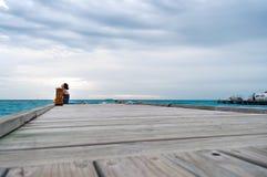 Frau am Ende von schließend Augen und oben von schauen des Piers Lizenzfreie Stockfotografie