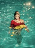 Frau entspannen sich im Badekurortpool Sommerferien und -reise zum Ozean Vitamin in der Banane am Mädchen, das nahe Wasser sitzt  Lizenzfreies Stockbild
