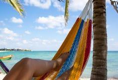 Frau entspannt sich in einer Hängematte auf einem karibischen Strand Stockfotos