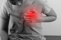 Frau erfasst ihren Kasten, möglichen Herzinfarkt der akuten Schmerz lizenzfreie stockfotografie