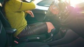 Frau erhält im Auto und befestigenden im Kindersitzgurt beim vom Fahrzeug bevor sie nach innen sitzen fährt stock video footage