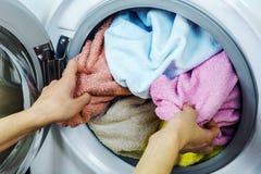 Frau erhält Kleidung von der Waschmaschine Stockfotos