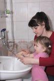 Frau erlernt das Mädchen, um Hände zu waschen stockbild