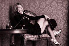 Frau ersucht um ein altes Telefon lizenzfreie stockfotos