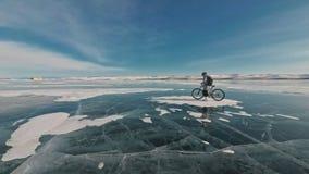 Frau fährt Fahrrad auf das Eis Das Mädchen wird in einer silbrigen unten Jacke, in einem Radfahrenrucksack und in einem Sturzhelm stock video footage